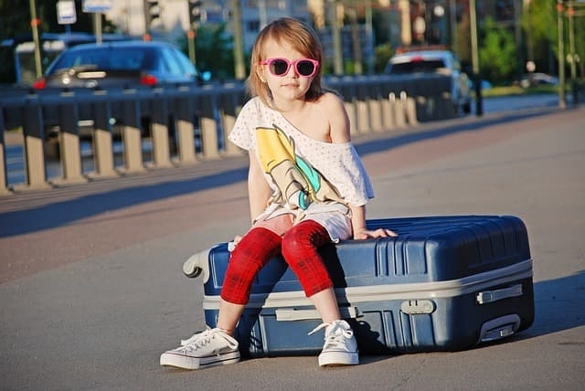 bambina in viaggio con valigia